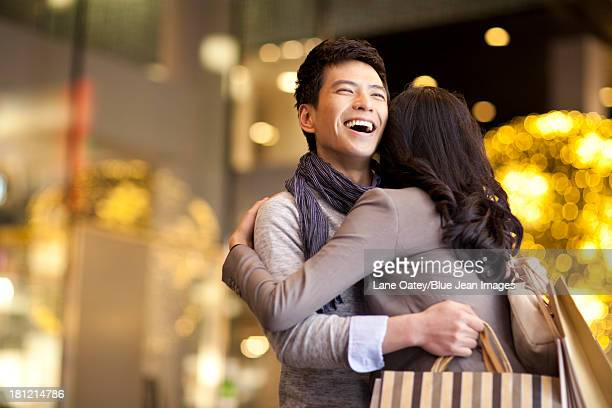 Sweet young couple embracing with shopping bags in hands