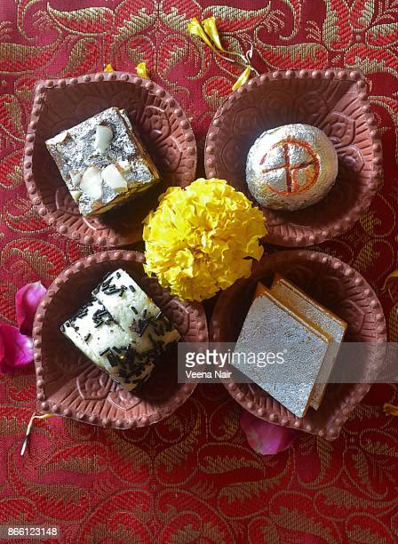 sweets arranged  in a clay diya with marigold flowers/diwali/deepavali - diwali sweets stock photos and pictures