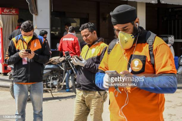 Swiggy delivery men check their mobile phones to deliver food commodities during a governmentimposed nationwide lockdown as a preventive measure...