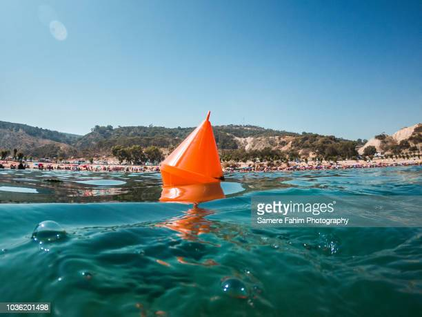 swim area buoy floating on water against a blue sky - buoy stock photos and pictures