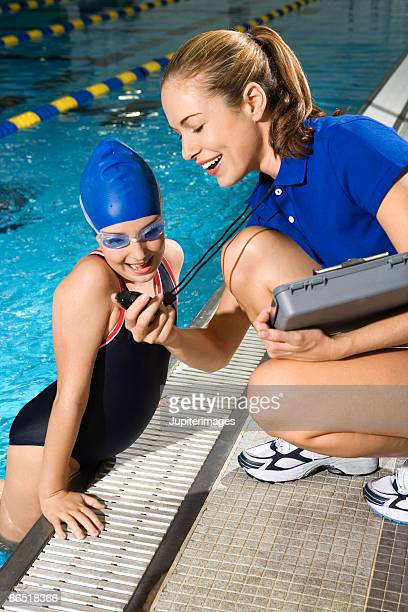 Swim coach showing girl her time on stopwatch