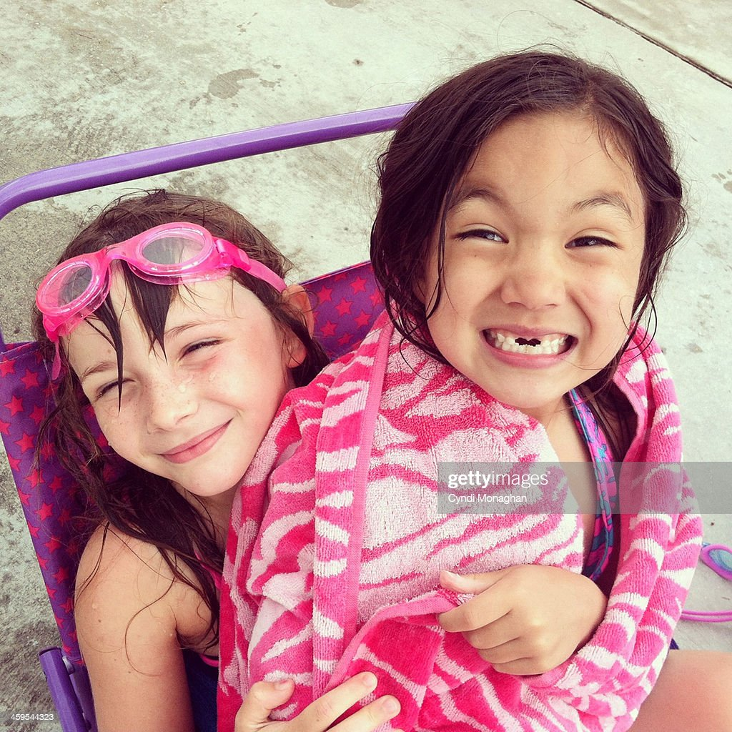 Two happy, little girls hugging at the pool. Best friends. Friendship. Childhood. Kids. Bathing suits. Swimming. Goggles. Pink towel. Smiles.