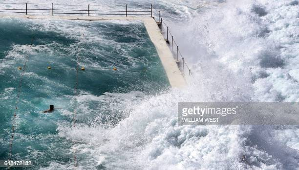 TOPSHOT A swimmer at Bondi's ocean pool watches as a big wave pours into the pool as large seas pound the coast at Bondi Beach in Sydney on March 6...