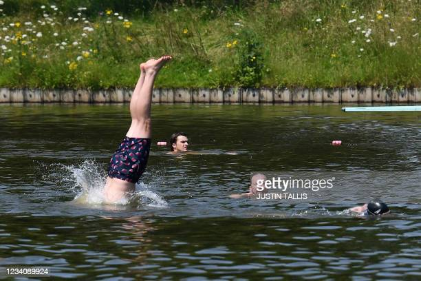 Swimmer dives into the water at Hampstead Heath men's bathing pond in London on July 21, 2021 as temperatures remain high in the country.
