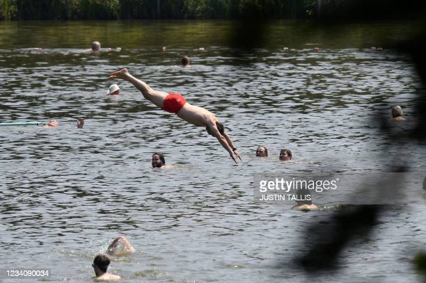 Swimmer dives into the water at the men's bathing pond in Hampstead Heath in London on July 21, 2021 as temperatures remain high across the country.