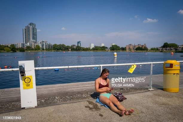 Swimmer dries out in the sun at the West Reservoir Centre in north London on August 11, 2020 during a Summer heatwave. - The water temperature at the...