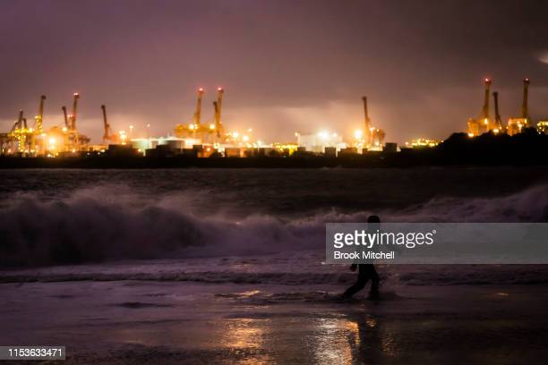 A swimmer enjoys rare waves breaking inside Botany Bay after dark on June 04 2019 in Sydney Australia The Bureau of Meteorology issued a severe...