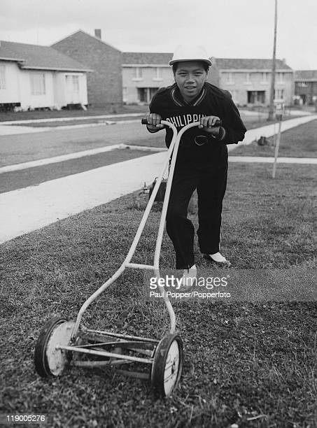 Swimmer Gertrudes Lozada of the Philippines team mows a lawn in the women's section of the Olympic Village in Heidelberg, Melbourne, before the...