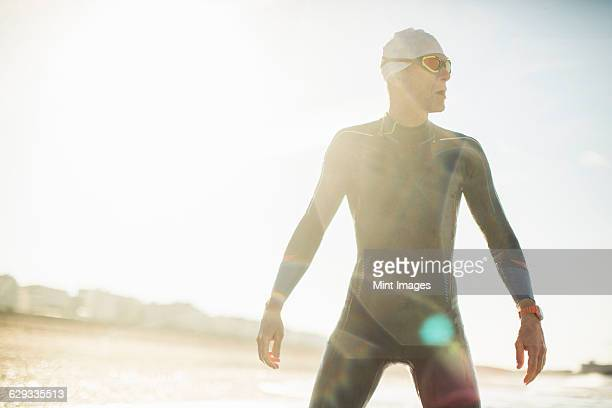 A swimmer in a wet suit, swimming hat and goggles on a beach.