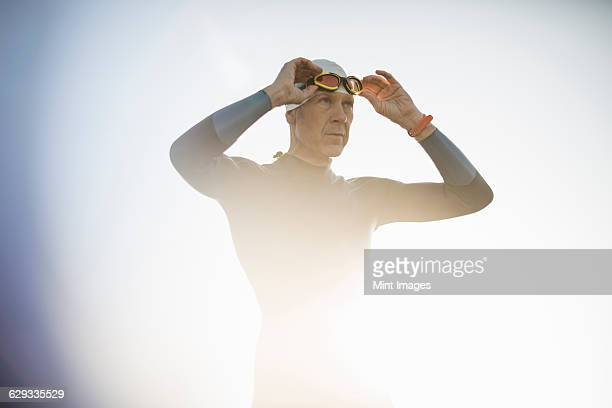 A swimmer in a wetsuit and swimming hat, adjusting his swimming goggles.