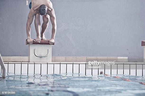Swimmer in indoor pool in starting position