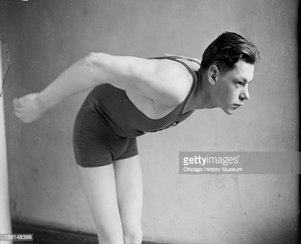 Swimmer John Weissmuller leaning forward standing in front of a backdrop in a room Chicago Illinois 1922