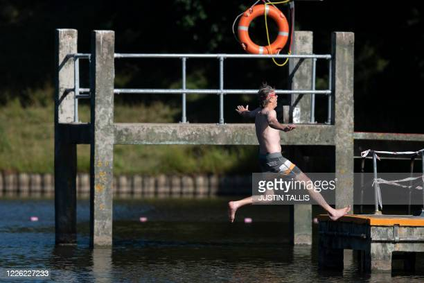 Swimmer jumps into the water backwards at the Hampstead Heath men's bathing pond in London on July 11 as restrictions are further eased during the...