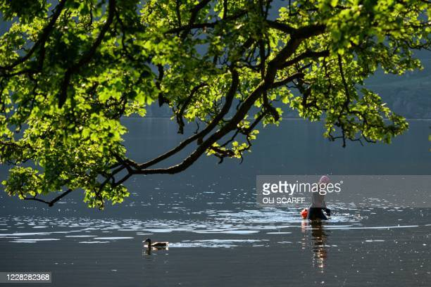 Swimmer leaves Ullswater in the sunshine near Glenridding in the Lake District in north west England on Bank Holiday Monday, August 31 as many people...