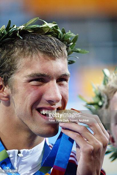 Swimmer Michael Phelps of the United States bites his gold medal playfully after taking the top prize in the 400meter individual medley at the...