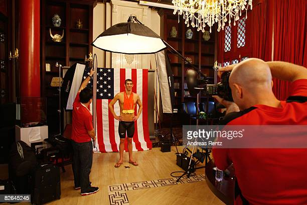 Swimmer Michael Phelps of the United States prepares for a photo shoot with his eight gold medals, all won in competition during the Beijing 2008...