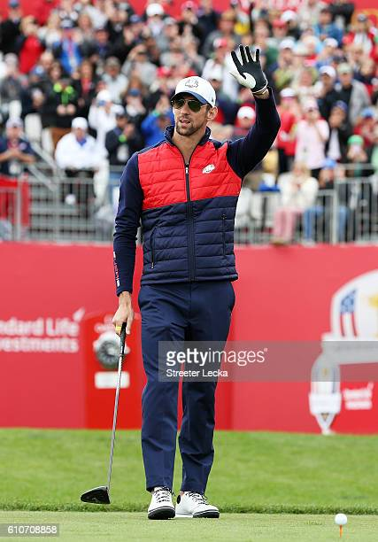 Swimmer Michael Phelps of the United States waves as he prepares to hit off the first tee during the 2016 Ryder Cup Celebrity Matches at Hazeltine...