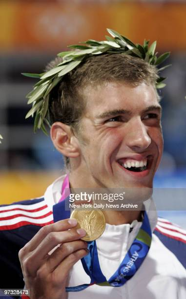 Swimmer Michael Phelps shows off his gold medal after coming in first in the 100meter butterfly final at the Aquatic Center during the 2004 Summer...