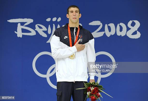 US swimmer Michael Phelps stands on the podium for the men's 100m butterfly swimming final medal ceremony at the National Aquatics Center during the...