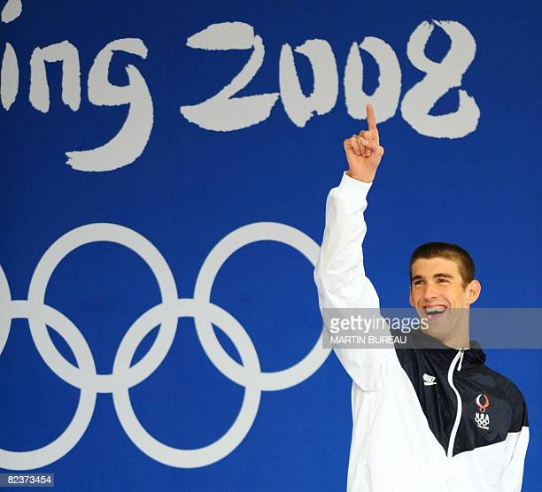 US swimmer Michael Phelps stands on the podium for the men's 100m butterfly swimming final during the medal ceremony at the National Aquatics Center...