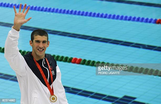 US swimmer Michael Phelps waves after the men's 100m butterfly swimming final medal ceremony at the National Aquatics Center during the 2008 Beijing...
