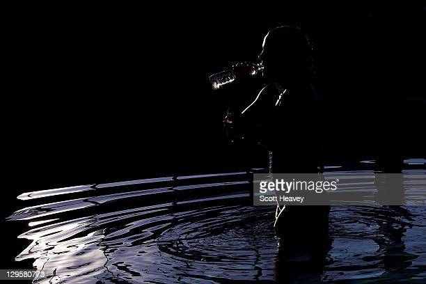 Swimmer Michelle McKeehan of the United States drinks water in the bathing pool before the start of the evening session during Day Four of the XVI...