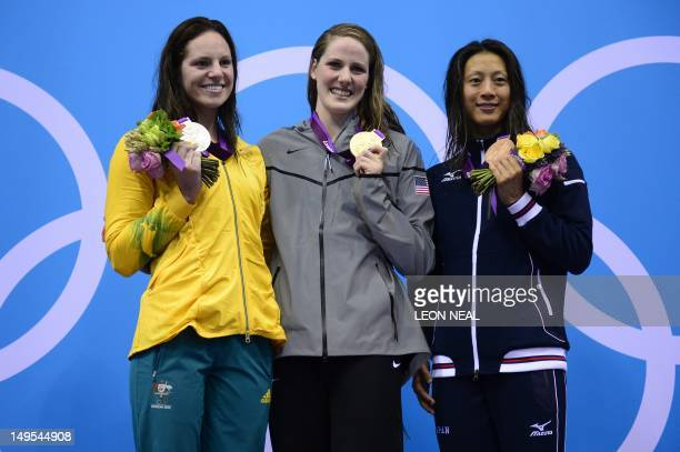 US swimmer Missy Franklin poses on the podium with the gold medal flanked by silver medalist Russia's Anastasia Zueva and bronze medalist Japan's Aya...