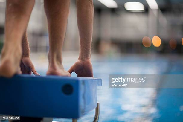swimmer on starting block at indoor swimming pool - eröffnung stock-fotos und bilder