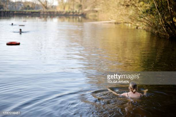 Swimmer paddles in the water at the Hampstead Heath ponds in London on March 30 as Covid-19 lockdown restrictions ease to allow outdoor activities,