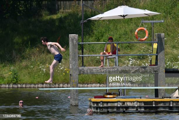 Swimmer prepares to dive into the water at the men's bathing pond in Hampstead Heath in London on July 21, 2021 as temperatures remain high across...
