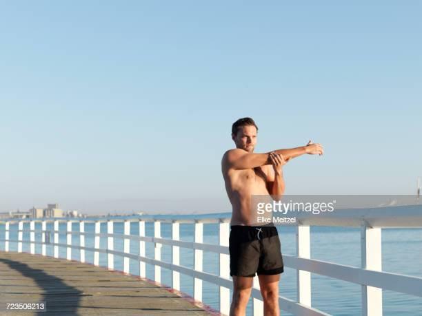 Swimmer stretching on boardwalk, Eastern Beach, Geelong, Victoria, Australia