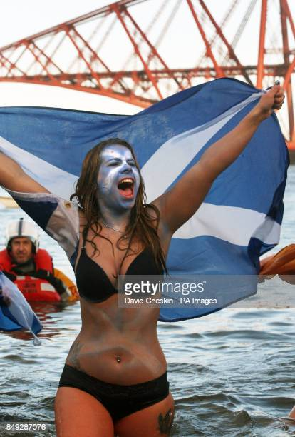 A swimmer takes part in the Loony Dook New YearOtildes Day swim in the river Forth near the Forth Rail Bridge