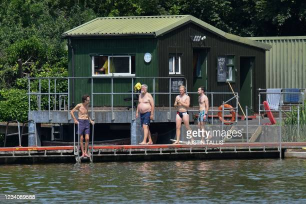 Swimmer walk to the water at the men's bathing pond in Hampstead Heath in London on July 21, 2021 as temperatures remain high across the country.