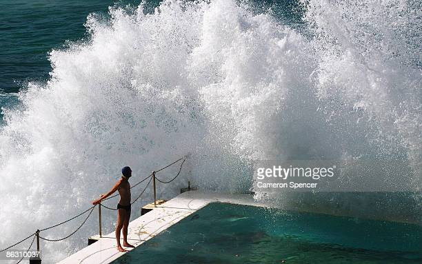 A swimmer watches a wave crash over him as he prepares to dive into the Icebergs ocean pool at Bondi Beach on May 1 2009 in Sydney Australia