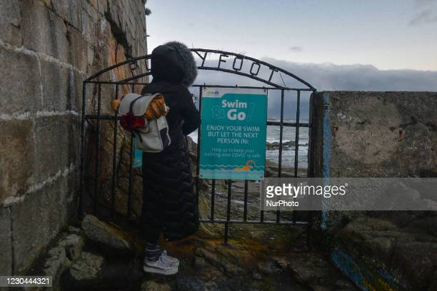 Swimmer watches the sea at the Forty Foot iconic promontory on the southern tip of Dublin Bay at Sandycove, during COVID-19 level 5 lockdown. The...