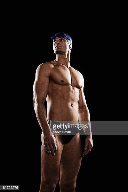 swimmer wearing cap and goggles - young men in speedos stock photos and pictures