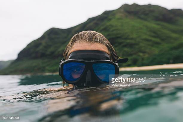 Swimmer wearing goggles near surface of sea