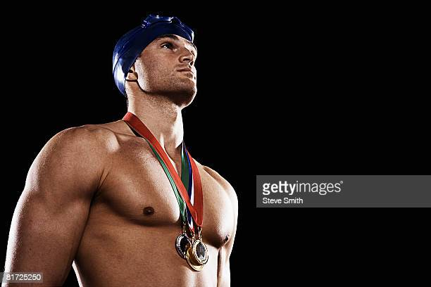 Swimmer with three medals wearing cap and goggles