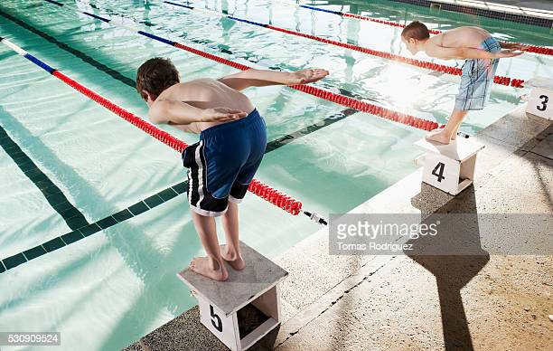 Swimmers about to jump in swimming pool