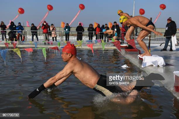 TOPSHOT Swimmers compete during an ice swimming contest in a pool carved from the frozen ice of the Songhua river during the annual Harbin Ice and...
