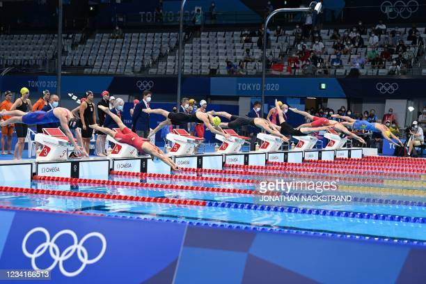 Swimmers compete in the final of the women's 4x100m freestyle relay swimming event during the Tokyo 2020 Olympic Games at the Tokyo Aquatics Centre...