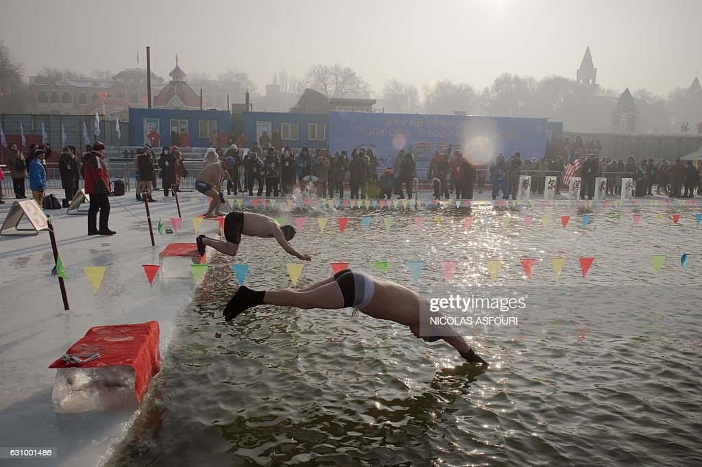 Swimmers dive into a pool cut from the frozen riverbank as part of a winter swimming competition during the 33rd Harbin Ice and Snow festival in Harbin on January 5, 2017. / AFP / Nicolas ASFOURI