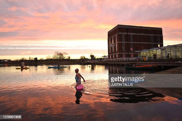 Swimmers enjoy a 'dawn dip' in the West Reservoir outdoor swimming lake in east London on December 2, 2020 as England emerges from a month-long...