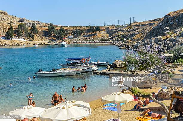swimmers enjoy azure waters in rhodes, greece - rhodes dodecanese islands stock photos and pictures