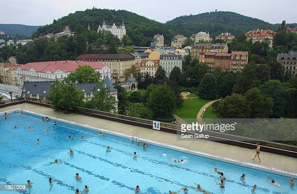 Swimmers enjoy the rooftop pool of the Hotel Thermal August 7, 2002 in the spa town of Karlovy Vary, Czech Republic. Karlovy Vary, known for its...