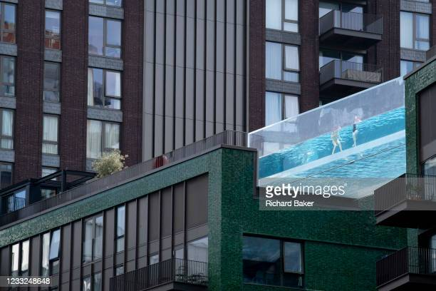 Swimmers enjoy the waters of the Sky Pool, a 25 metres-long transparent water pool bridging two 10-storey residential towers 35 metres above the...