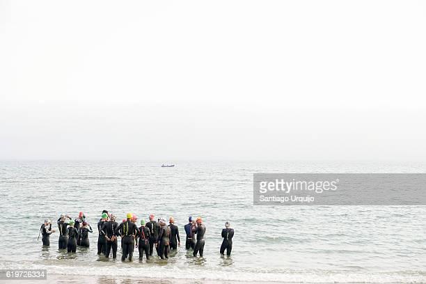 Swimmers entering the water at beach of Santa Cristina