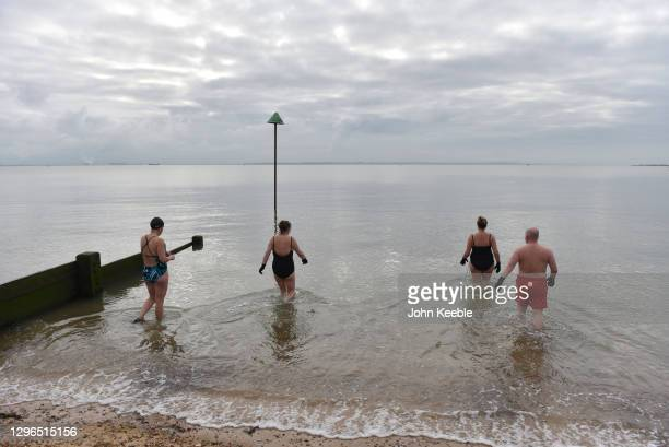 Swimmers exercise with a socially distanced cold water swim at Chalkwell Beach on January 15, 2021 in Southend, England. With a surge of covid-19...