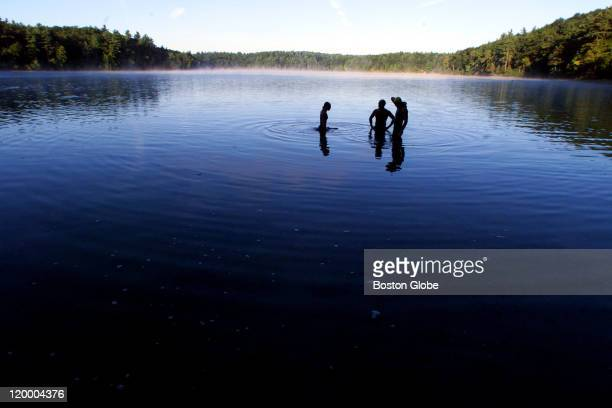 Swimmers Florence Chretien of Natick Rob Sczupak of Natick and Drew Gronewold of Somerville leave the water an early morning swim in the pond