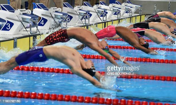 Swimmers from Colombia, Brazil, Puerto Rico, USA, Canada and Aruba participate in the Men's Swimming 100m Backstroke Final A during the Lima 2019...